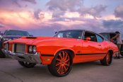 Trendsetting Red Oldsmobile Cutlass Rolling on Color Matched Forgiato Wheels